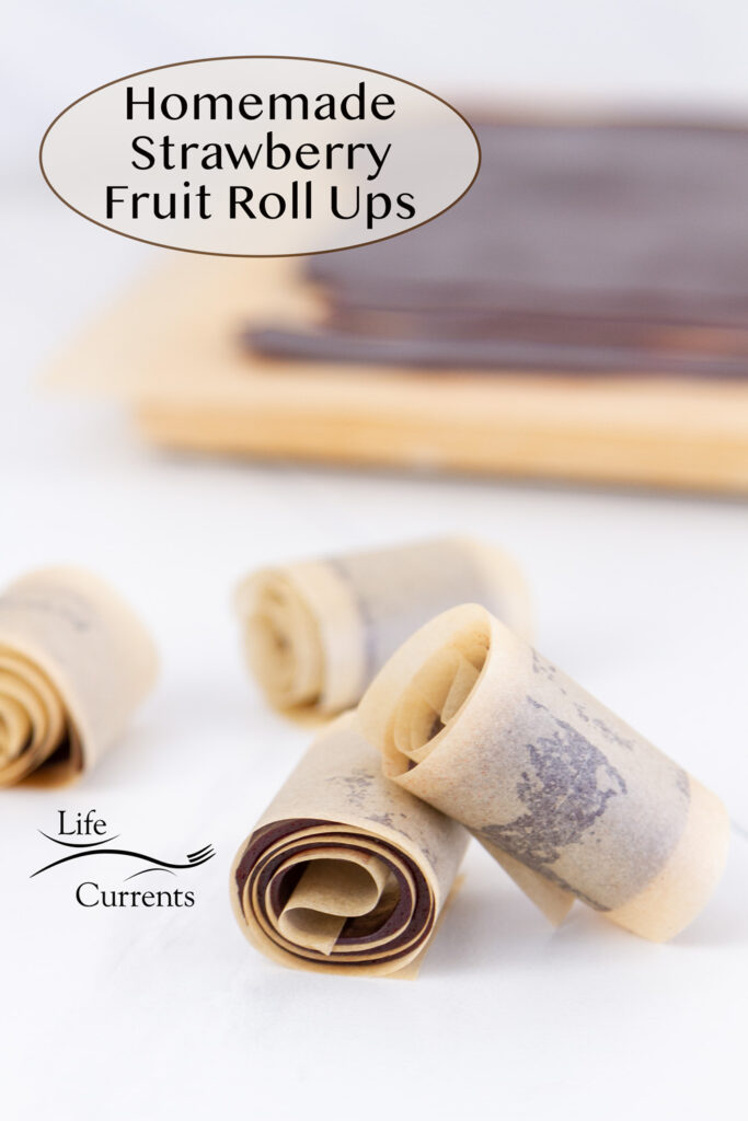 strawberry fruit roll ups in parchment paper in front of a cutting board with the rest of the fruit smash on it, title on upper left of image.