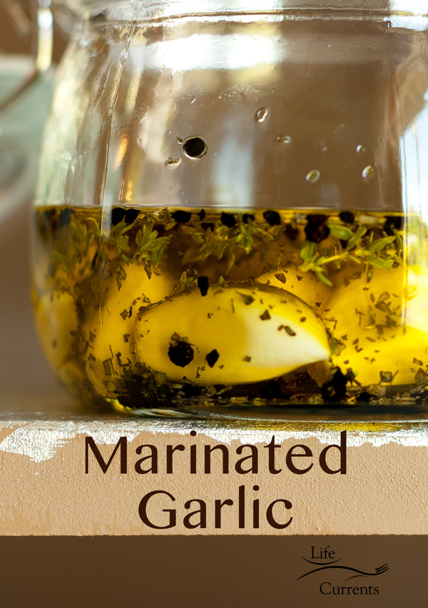 A side view of the Herb & Spice Marinated Garlic in a glass jar on the edge of a table