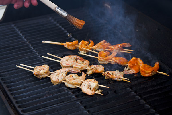 mop sauce being brushed on the shrimp: Spicy Grilled Buf-a-que Shrimp in a Buffalo-style mop sauce #grilled #spicy #shrimp Life Currents https://lifecurrentsblog.com