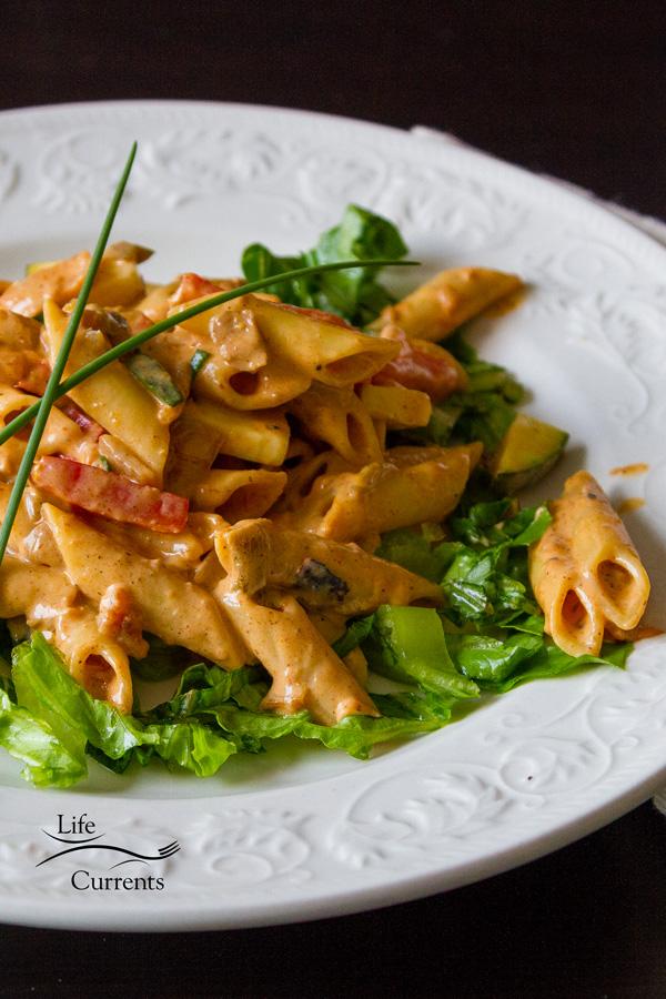 pasta dinner served on shredded lettuce on a white plate on a black background