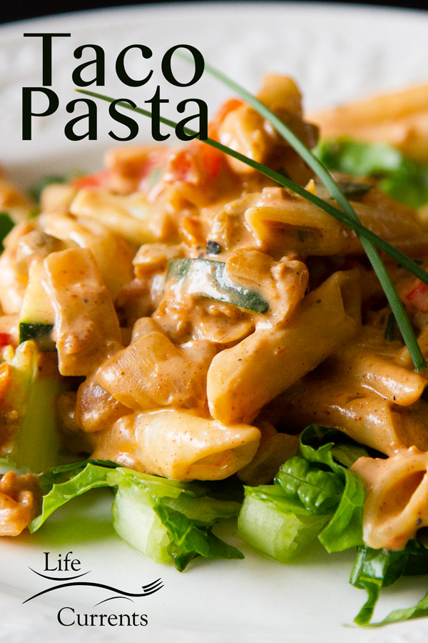 Taco psata dinner with pasta and veggies in a creamy red sauce on shredded lettuce on a white plate with the title