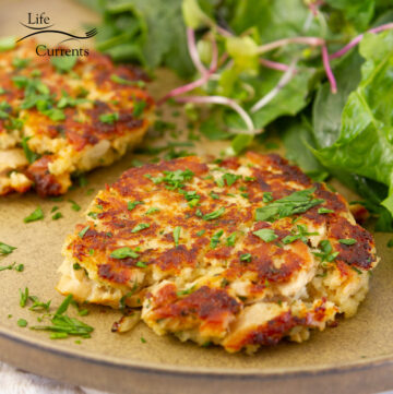 square crop of two tuna cakes on a plate with herbs and fresh greens.