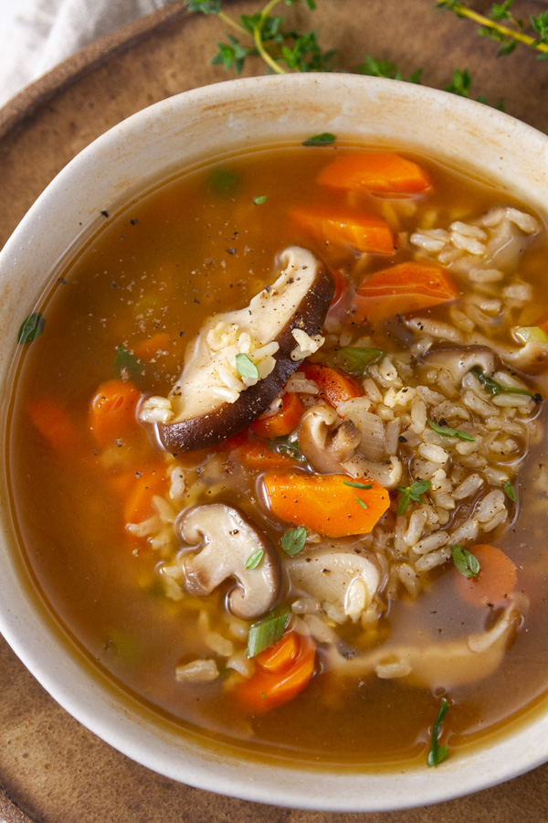 top down view of a bowl of vegetable soup with brown rice