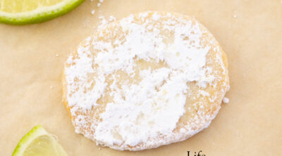 a cookie coated in powdered sugar with slices of lime around it.