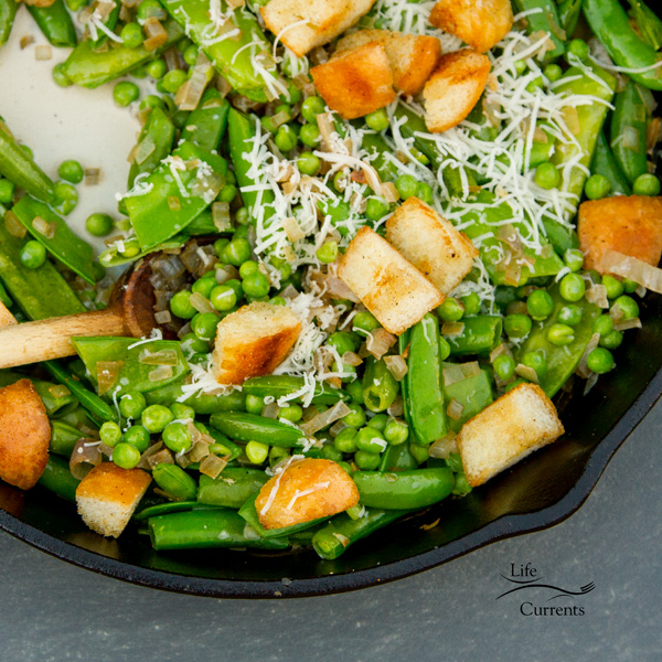peas, croutons, and parmesan cheese in a cast iron skillet