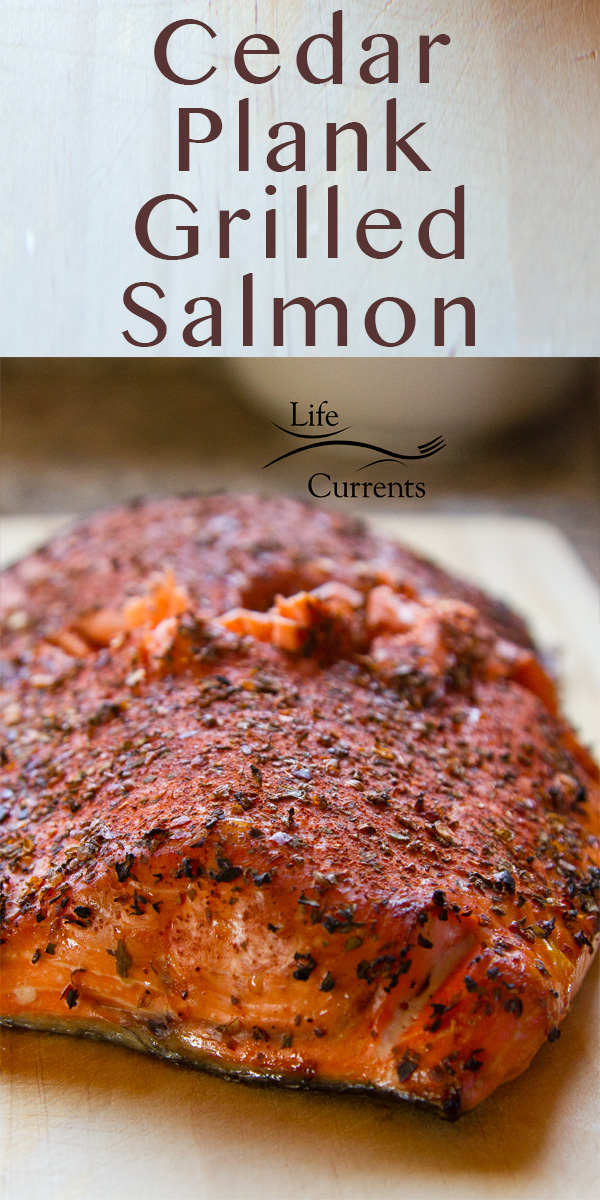 close up on a piece of cedar plank grilled salmon with seasoning on a wooden board with the title Cedar Plank Grilled Salmon at the top