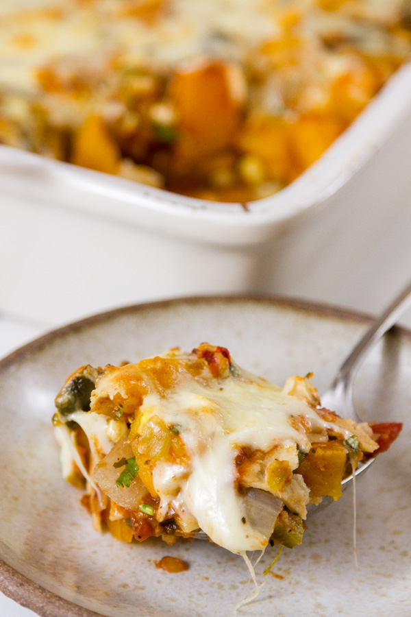 serving up a portion of butternut squash casserole onto a smaller plate with the casserole dish in the background