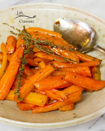 square crop of carrots on a plate with a serving spoon and garnished with thyme