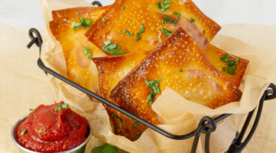 square crop of pizza rolls in a wire container with a side of pizza sauce and some fresh basil.