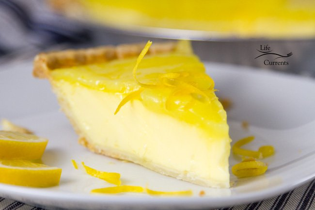 Grandma's Lemon Custard Pie with Lemon Curd Topping - a slice of lemon custard pie on a plate with blue ticking in the background