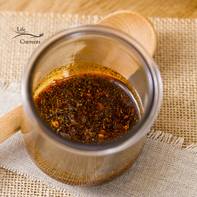 Cajun Spice Oil in a glass jar with a wooden spoon