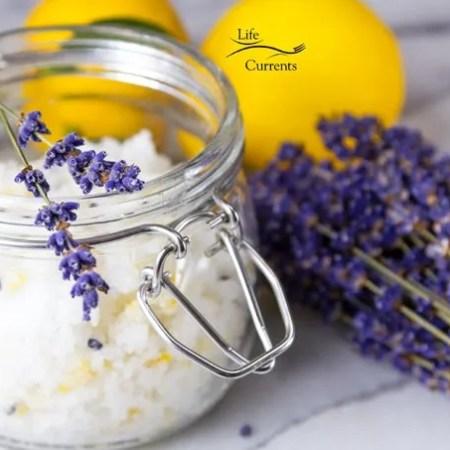 Lemon Coconut Sugar Scrub in a glass jar with lavender flower bundle and lemons