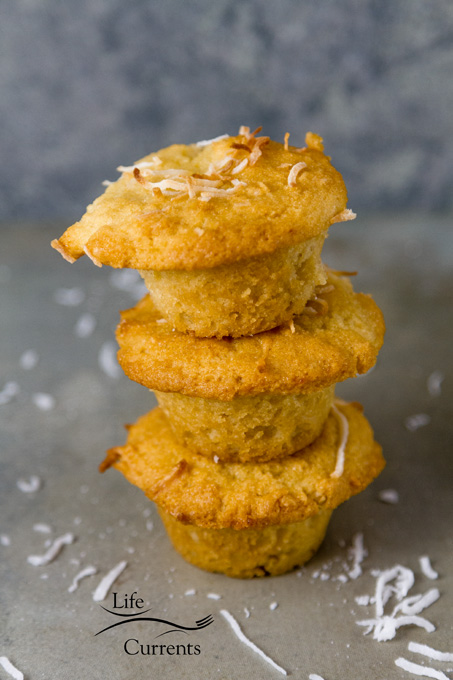 Gluten-Free Coconut Muffins stacked 3 high on a grey background