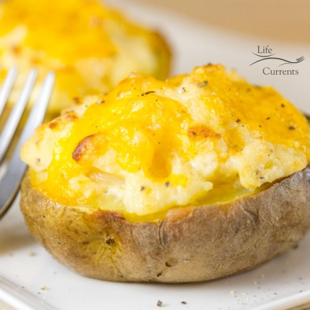 Twice Baked Potatoes - This simple, easy to make in the oven, potato side dish recipe is the perfect cheesy make ahead accompaniment to dinner that's also perfect for a crowd.