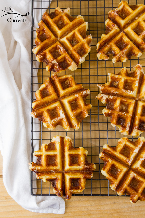 Belgian Liège Waffles are filled with caramelized pockets of Belgian pearl sugar and baked to crispy perfection - cooling on a rack