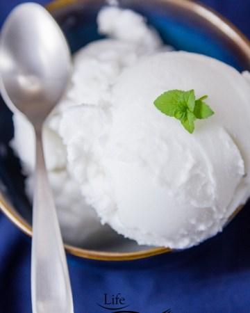 creamy and delicious white coconut sorbet scooped high in a blue bowl with a silver spoon and a mint leaves for garnish