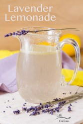 Lavender Lemonade in a hand blown glass pitcher with sprigs of lavender around. Lots of yellow and purple colors