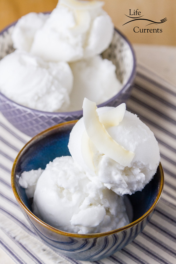 Two small bowls of coconut sorbet, the one in front is blue and the one in back is lavender colored. Both on a striped blue cloth