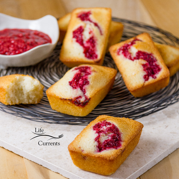 French Almond Financiers Cakes served with roasted raspberry sauce on the side all on a swirly wire rack