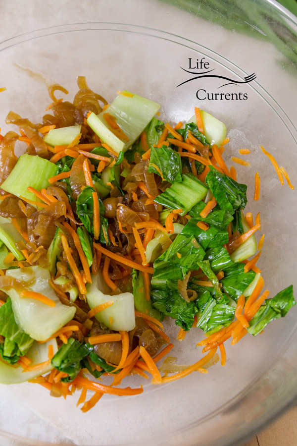 stir fried bok choy, carrots, and shallots in a glass bowl