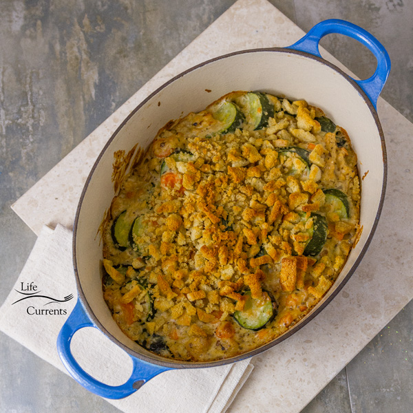 Zucchini Stuffing Casserole Recipe fresh out of the oven and ready to eat in the blue casserole dish on a white serving tray