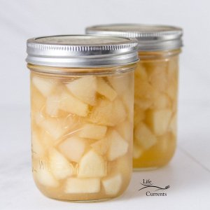two jars of oven canned peach preserves on a white background