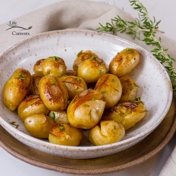 Cooked baby Yukon Gold potatoes with crispy browned edges in a white bowl on a brown bowl with fresh rosemary in the background