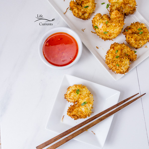 Air Fryer Coconut Shrimp with red dipping sauce on a white background with wooden chopsticks