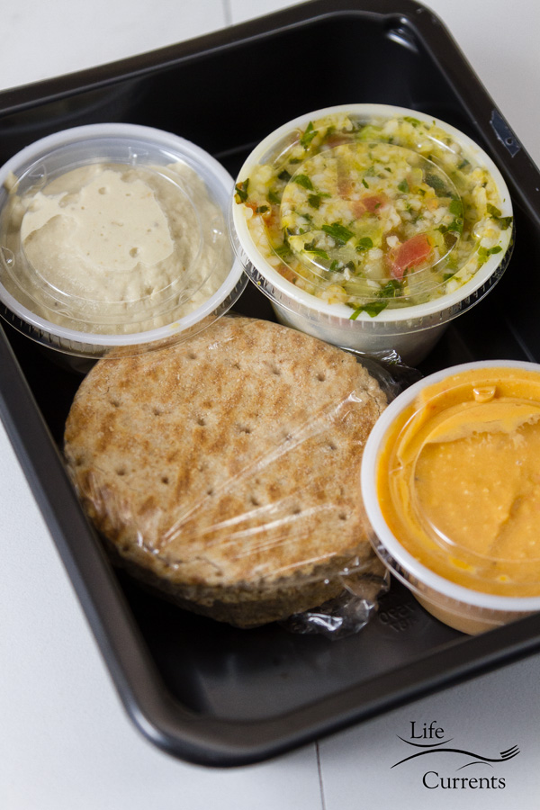 Lunch: Mediterranean Tapas, Red Pepper Hummus, Baba Ghanouj, Tabbouleh, and Whole Wheat Pita Bread in a meal prep black plastic tray