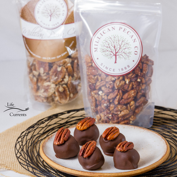 Pecan Bourbon Balls on a white plate in front of bags of pecans from Millican Pecan Company