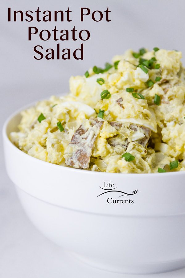 Potato salad in a white bowl on a white background topped with chives and the title is on the image