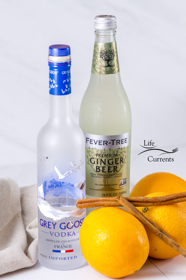 The ingredients for an Orange Cinnamon Moscow Mule: vodka, ginger beer, oranges, cinnamon all on a white background
