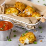 Air Fryer Mozzarella Bites served in a wire basket with a brown paper liner with one mozzarella bite in front, the cheese has oozed out a bit and served with a tin ramekin of marinara sauce