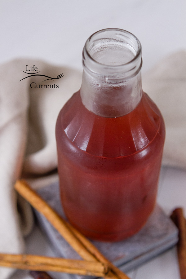 Cinnamon Simple Syrup in a glass jar on grey tiles with cannamon sticks at the bottom and a cloth napkin in the back