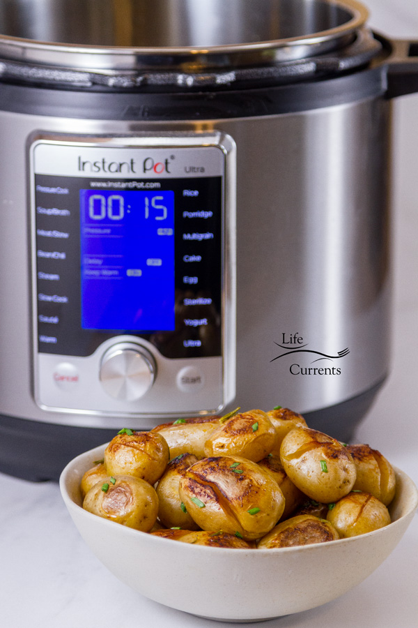 An Instant Pot in the background behind a small white bowl full of cooked potatoes