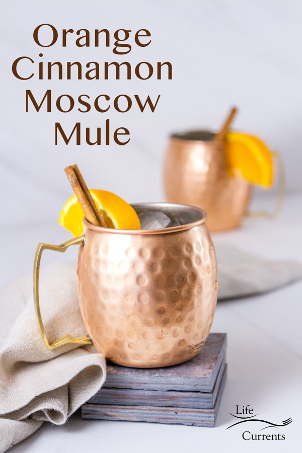 Two Moscow Mule drinks in copper mugs the front one is on a stack of grey tiles with a grey linen napkin and a title
