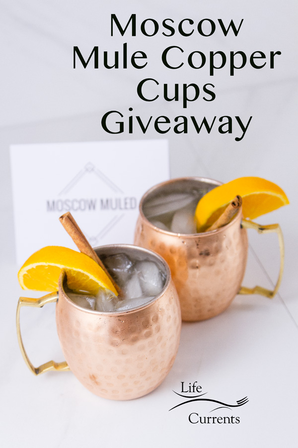 two copper mugs filled with beverages and ice garnished with orange slices and a title of Moscow Mule Copper Cups Giveaway and a card for Moscow Muled company