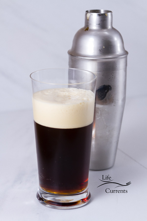 a tall glass of coffee with foam in front of a cocktail shaker on a white back gorund