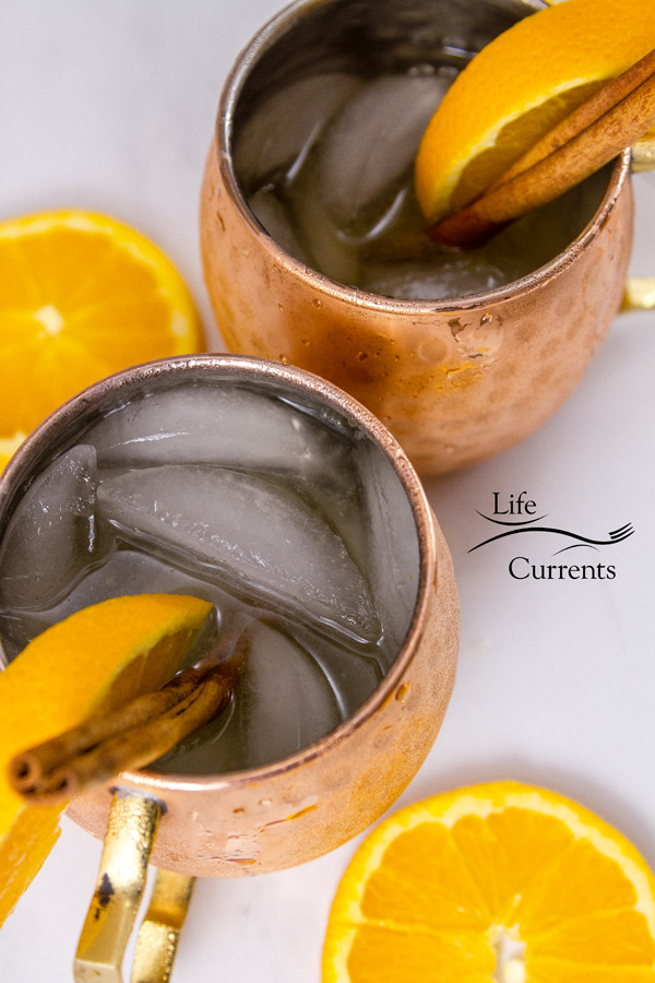 top down or flatlay of the Moscow Mule copper cups filled with ice and beverages with orange slices on a white background