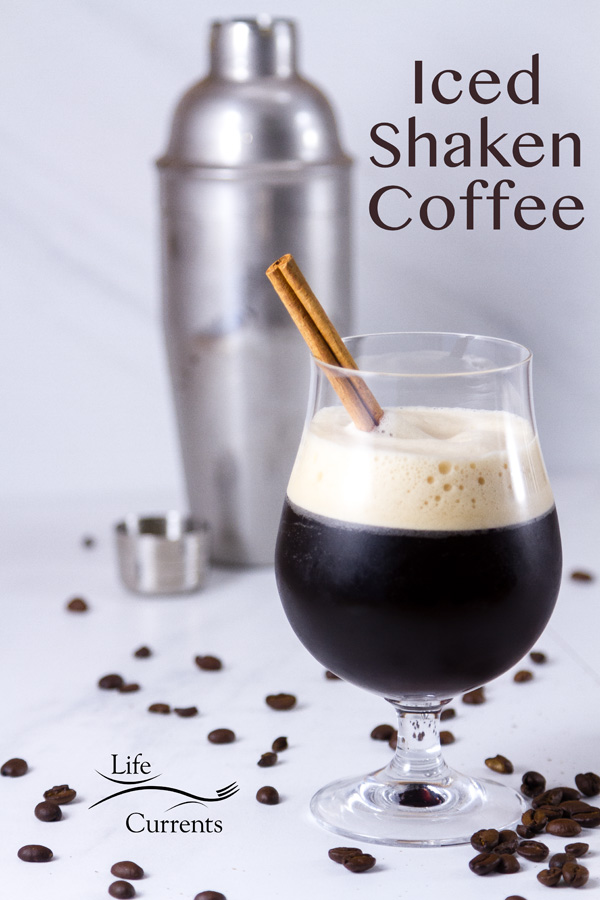 Iced Shaken Coffee with a foamy head in a glass with a cinnamon stick in front of a shaker on a white background with coffee beans around