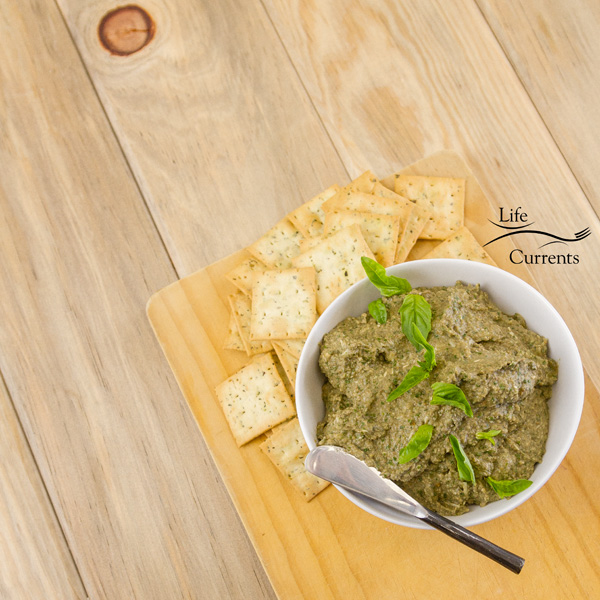 Mushroom Walnut Pesto in a white bowl served on a wooden cutting board with crackers all on a wood background