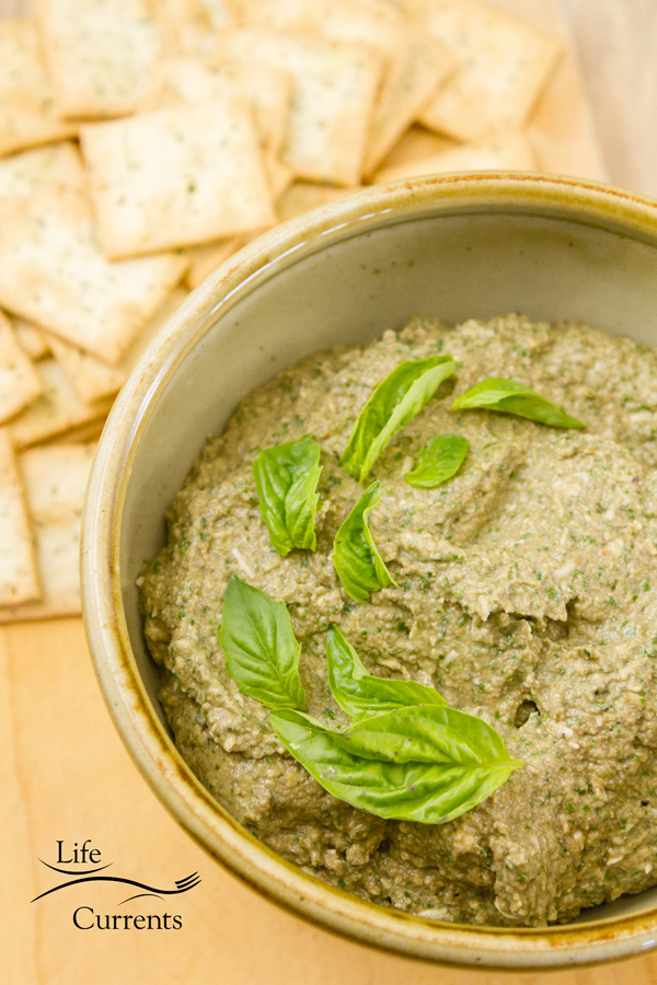 Mushrrom walnut basil pesto spread in an ivory bowl with crackers and fresh green basil leaves on a wood background