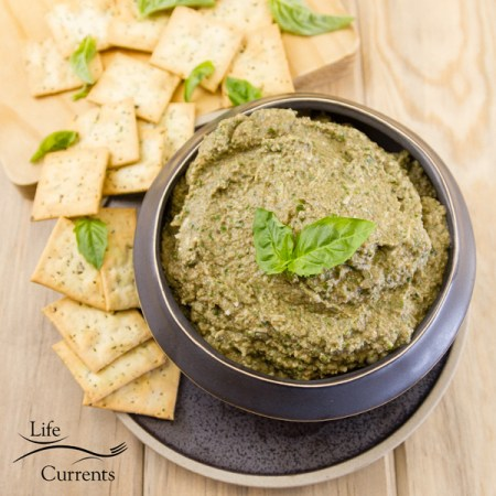 This Mushroom Walnut Pesto Spread in a black bowl on a small black plate with crackers and lots of green basil leaves