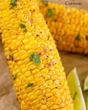 close up on the roasted air fried corn on the cob with green herbs for garnish and lime wedges and another cob in the background