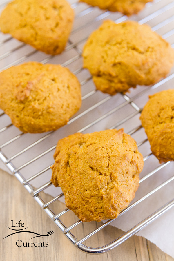 pumpkin cookies cooling on a rack with parchment paper in the background