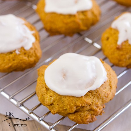 four iced pumpkin cookies on a cooling rack