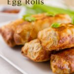 Egg Rolls stacked on a plate garnished with green onions. Plus the title