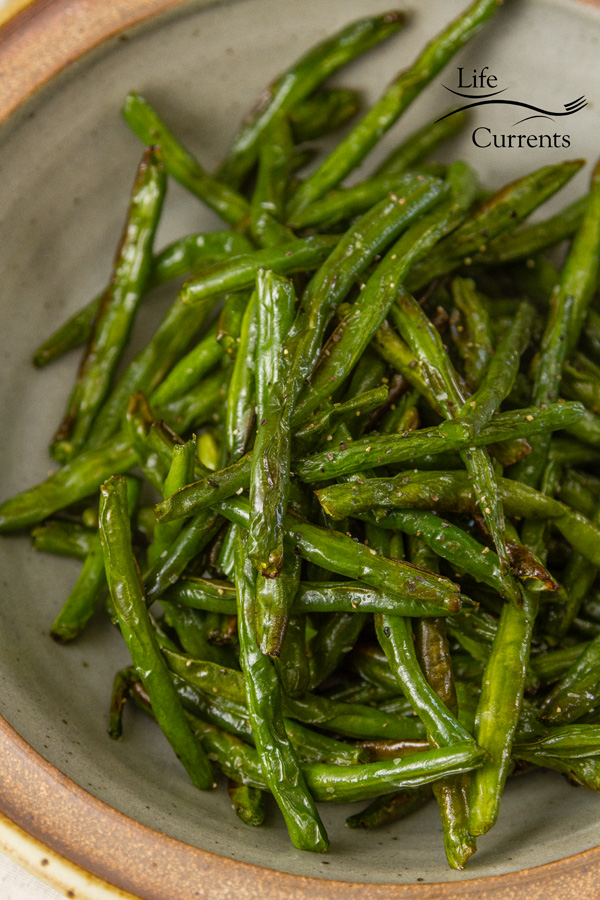 Air Fryer ROasted Green Beans in a white bowl with a terracotta rim