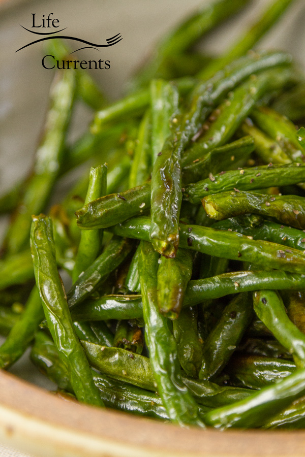 a close up on the roasted green beans showing the browning and the salt and pepper