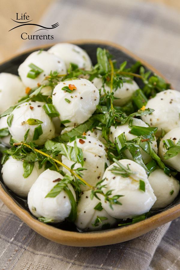fresh mozzarella Ciliegine with herbs in a dark bowl on a cloth napkin
